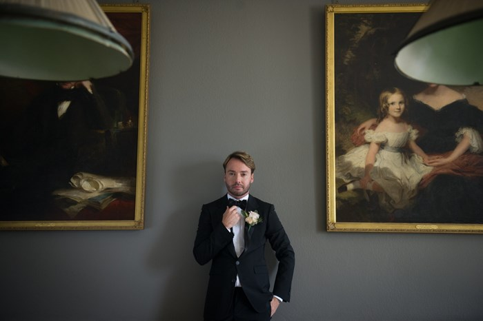 A Groom poses in the Billiard Room