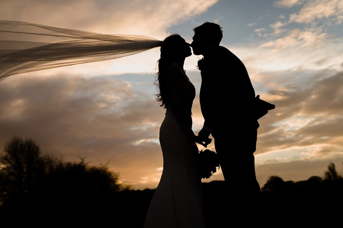 Bride and Groom at Sunset with flying vail
