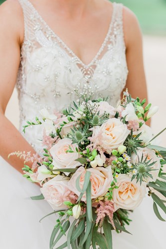 Beautiful brides bouquet with roses and thistle