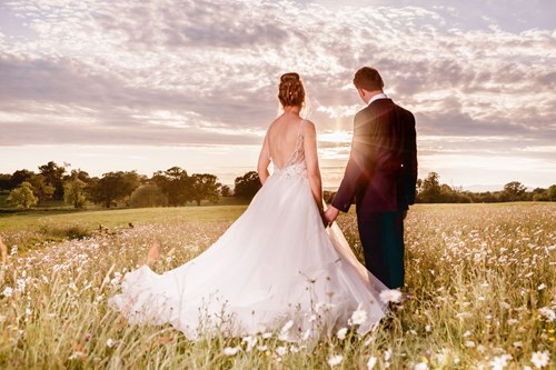 Bride and groom pose for a photograph at sunset