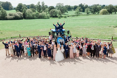 Bride and Groom pose by a tractor on their wedding day at Rockbeare Manor near Exeter