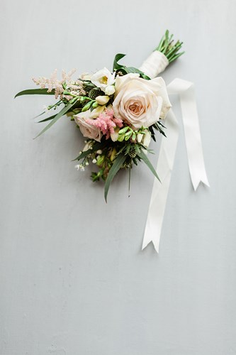 Bridal Bouquet Entwined in Ribbon Lay on a Plain Grey Background