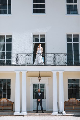 Bride stands on the Balcony above the Groom on the Porch