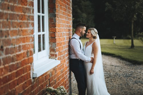 Bride and Groom Lean against a Brick Wall and Lean in for a Kiss
