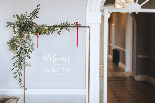 Rustic copper archway with a spray of flowers on the top left corner hangs a 'Welcome' sign in the Manor House's entrance