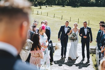 The Brides Brothers Walk her down the Aisle to her Groom as the Guests Watch with the Parkland Backdrop
