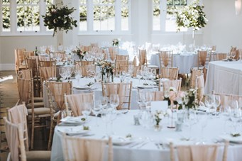 Ballroom Set for Dinner Dressed with Pink Blush Chair Sashes and Floral Geometric Centrepieces