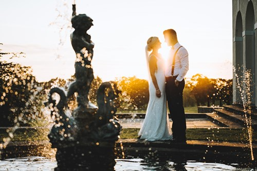 Bride and Groom Lean in for a Kiss With the Sun Pouring Between them as they Stand Behind a Fountain
