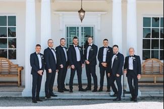 Groomsmen in Tuxedos Stand on the Front Porch at Rockbeare Manor Between the Pillars