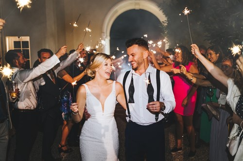 Bride and Groom Hold Sparklers and Celebrate as the Guests Hold up Sparklers