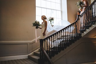 Bride Walks Down the Grand Staircase with her Bouquet in Hand as the Bridesmaids Trail Behind Holding her Vail