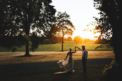 Bride and Groom Dancing in the Sunset Beneath the Trees