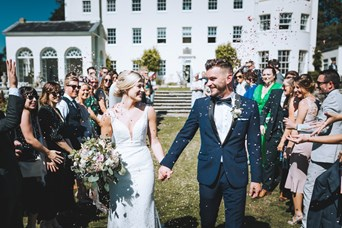 Bride and Groom Hold Hands and Smile at One Another as the Guests Throw Confetti