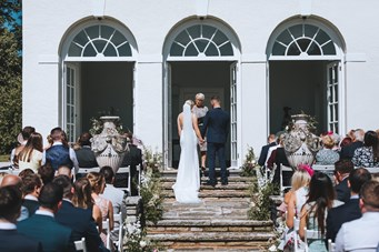 Bride and Groom stand on the Steps of the South Pavilion Saying their Vows as the Guests Watch from Below