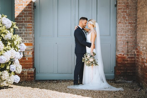 Bride and Groom Cuddle in front of the Barn Doors