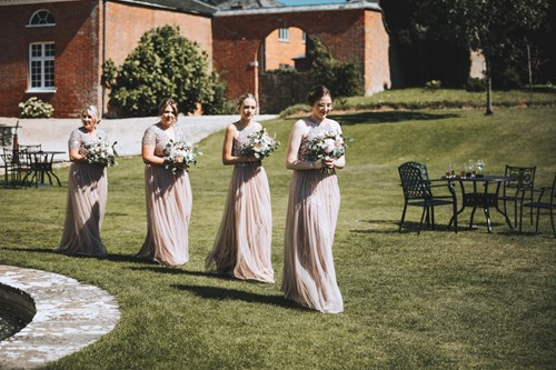 Bridesmaids walk across the lawn i na procession with their bouquets in hand