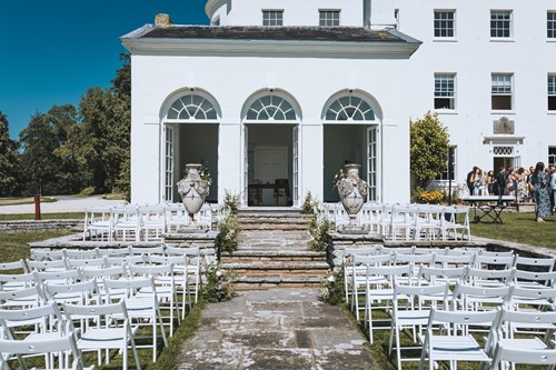 The South Pavilion of Rockbeare Manor set for an Outdoor Ceremony with beautiful white chairs